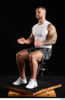 Grigory  1 camo shorts dressed sitting sports white sneakers white tank top whole body 0016.jpg